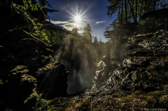Solen skinner over Gudbrandsjuvet mens elven kaster en del av vannet flere meter oppover bergveggen.