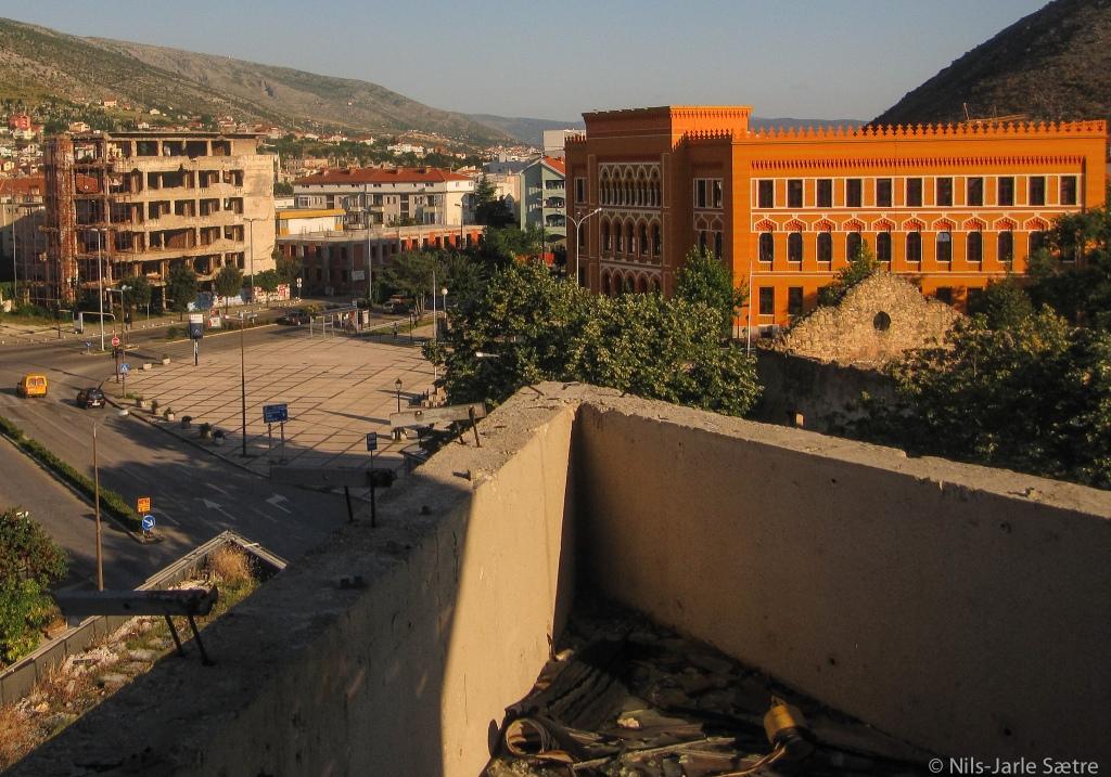 Gata som går på tvers var frontlinjen under krigen. På kroatisk står nå en videregående skole malt i oransje, mens det på den muslimske siden står et bygg som er bombet i stykker. Bildet er tatt fra der snikskytterne skjøt sine ofre.