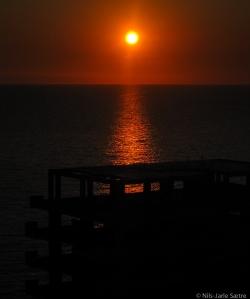 Solen i ferd med å gå ned bak et hotellet som er i ferd med å bli bygget ved sjøkanten.