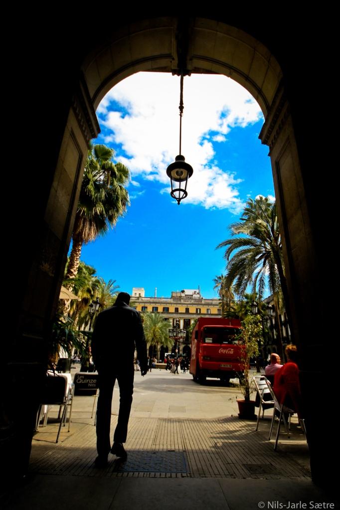 En mann er på vei ut av skyggen og inn i solen på Placa Reial.