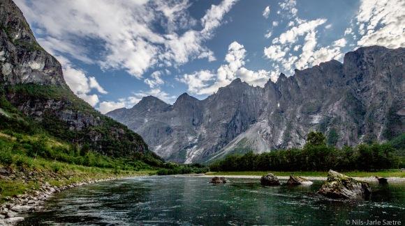 VAKKERT: Elva Rauma renner ned Romsdalen. Til høyre Trolltindene med Trollveggen omtrent midt i bildet. Den siste toppen til venstre i tinderekken er Breitinden (1.797moh, høyest av Trolltindene) og følger du fjellrekken videre er Mannen det neste fjellet. Men det er skjult av fjellveggen helt venstre som har Romsdalshornet som topp.