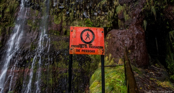 Til høyre er inngangen hvor  en låst dør stenger muligheten til å gå videre. Øverst på venstre side av skiltet er et lite svart området hvor man kunne gå bak fossen før.